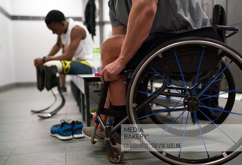 Paraplegic athlete in wheelchair in locker room