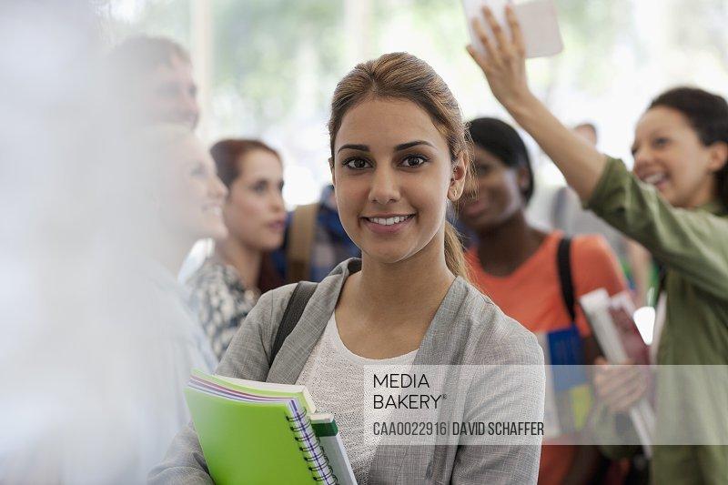Smiling female student holding books during break