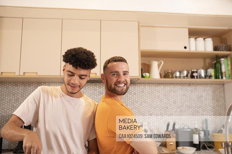 Portrait happy gay male couple in kitchen