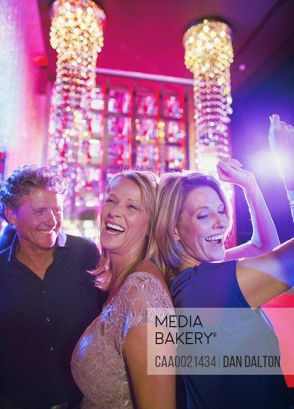 Women and man dancing in nightclub