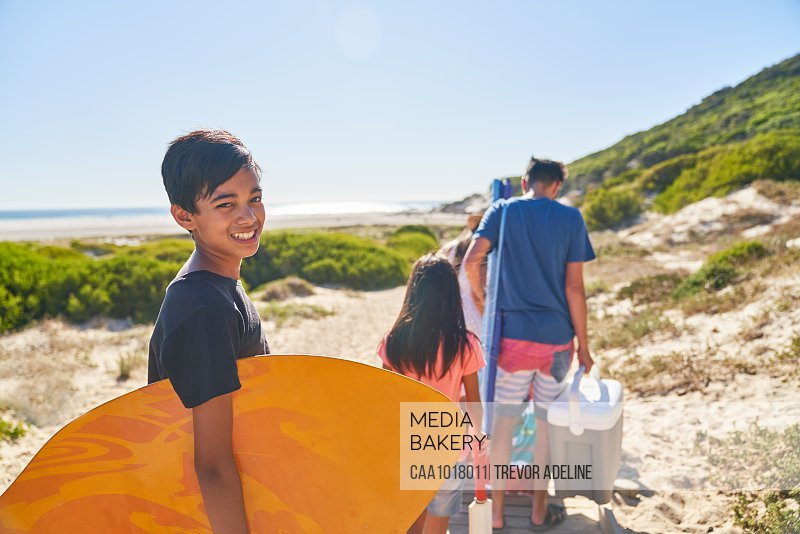 Portrait happy boy carrying bodyboard on sunny beach with family