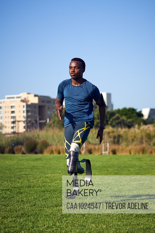 Focused young male amputee sprinter practicing in sunny grass