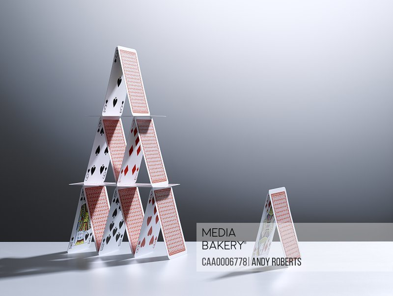 Small house of cards next to large house of cards
