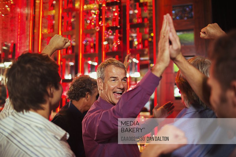 Men high fiving each other in nightclub