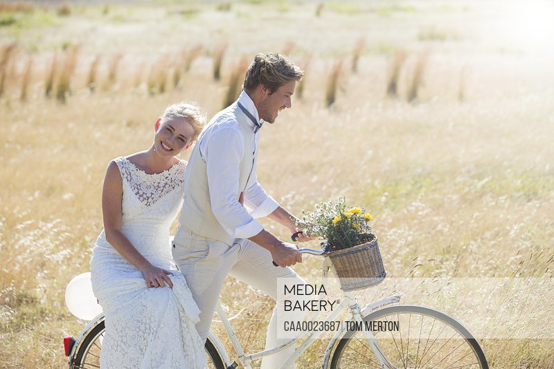 Young couple riding bike in meadow