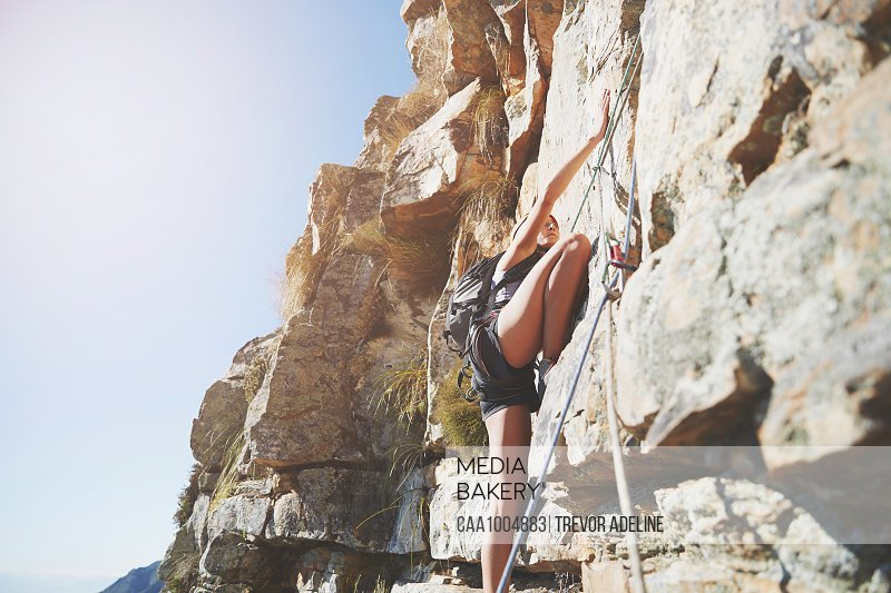 Female rock climber scaling rock