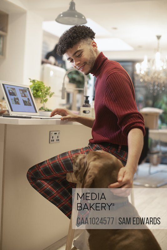 Young man working from home at laptop and petting dog in kitchen