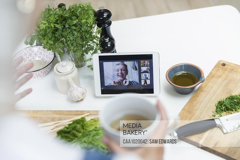 Woman drinking tea and cooking while video chatting with friends