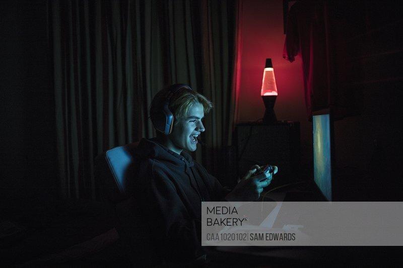Smiling teenage boy playing video game at computer in dark bedroom