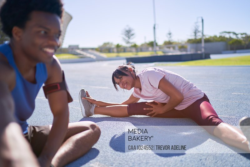Happy young runners stretching on sunny sports track