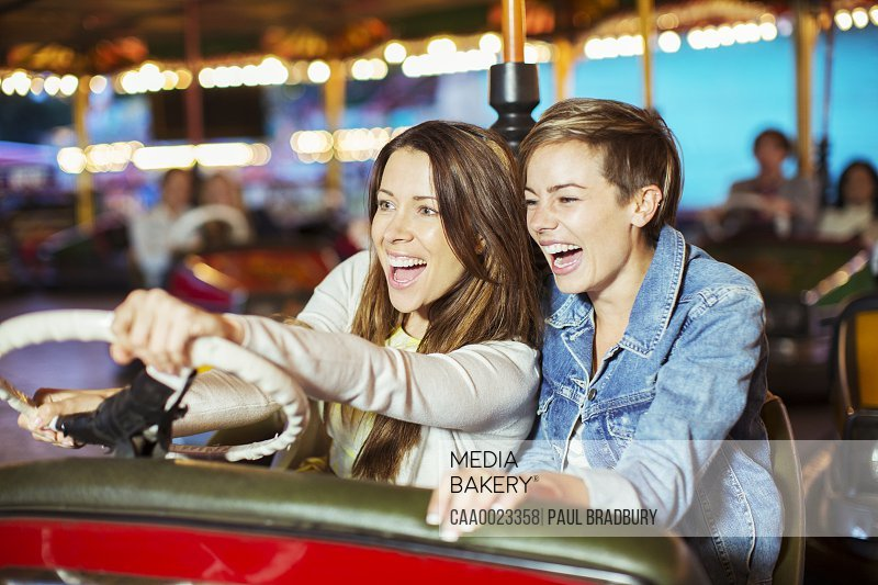Two cheerful women on bumper car ride in amusement park
