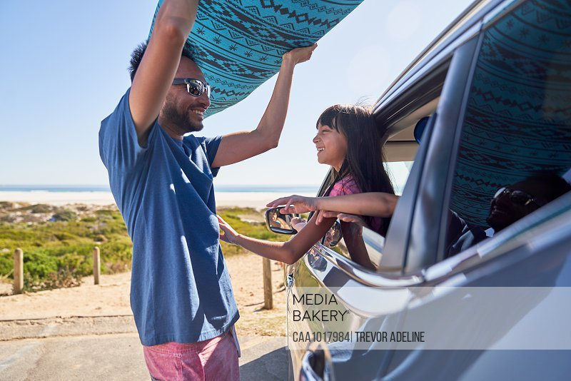 Daughter watching father remove surfboard from car at sunny beach
