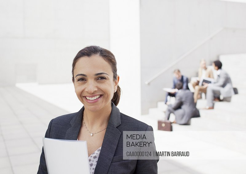 Portrait of confident businesswoman with co-workers in background
