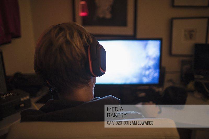 Teenage boy with headphones playing video game in dark bedroom