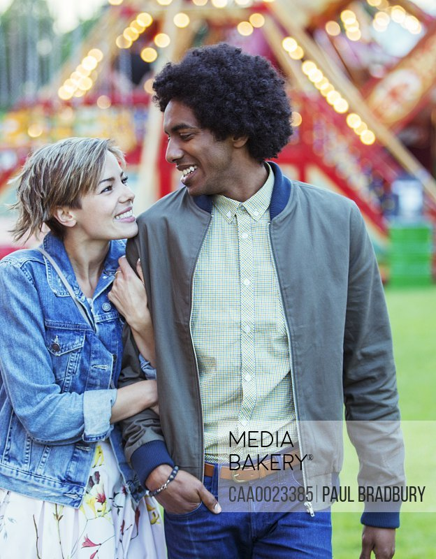 Young multiracial couple smiling to each other in amusement park