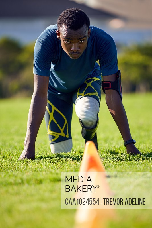 Focused amputee sprinter doing sports drills in grass