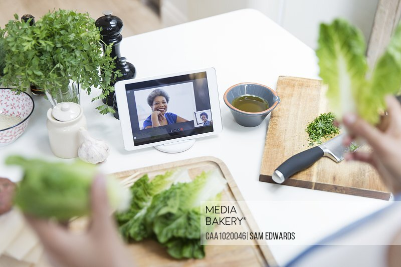 Woman with lettuce cooking and video chatting with friends in kitchen