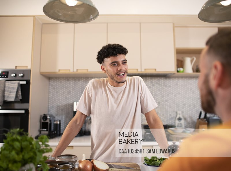 Gay male couple talking in kitchen