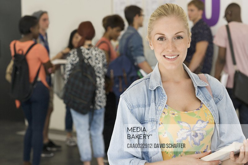 Smiling female student holding books other students in background