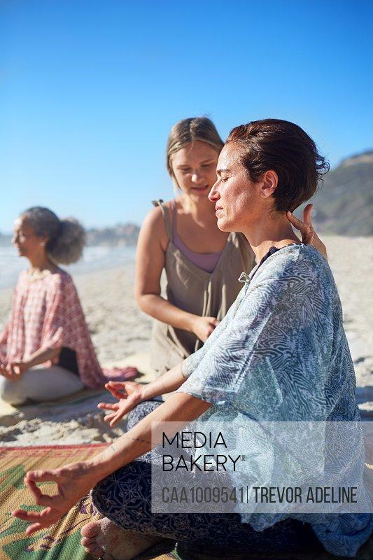 Serene woman meditating on sunny beach during yoga retreat