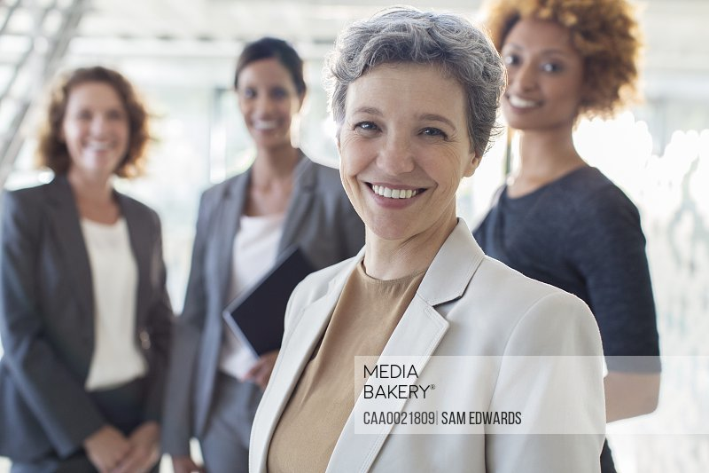 Portrait of smiling mature businesswoman with office team in background