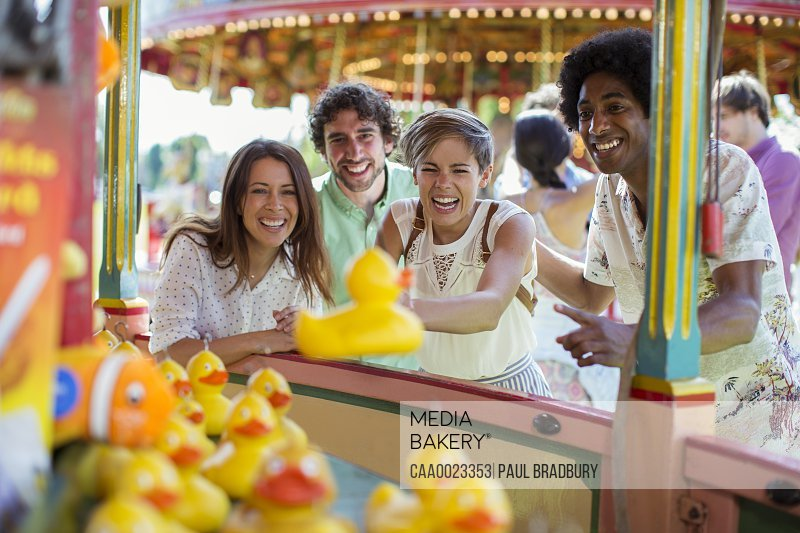 Group of friends having fun with fishing game in amusement park