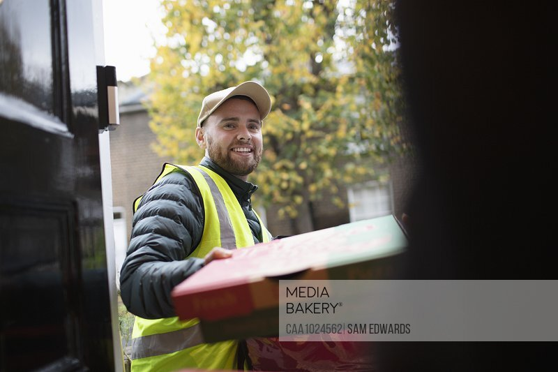 Friendly delivery man delivering pizza at front door