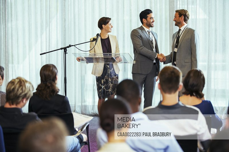Businessmen shaking hands during presentation in conference room businesswoman smiling