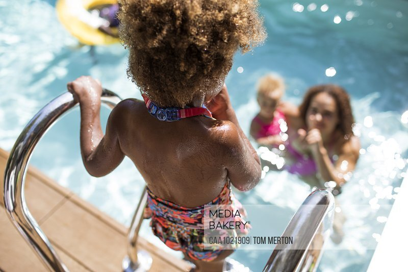 Mother watching daughter get into sunny summer swimming pool