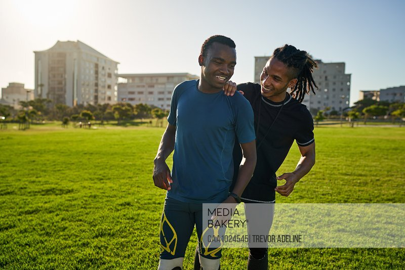 Happy coach and amputee athlete in sunny field