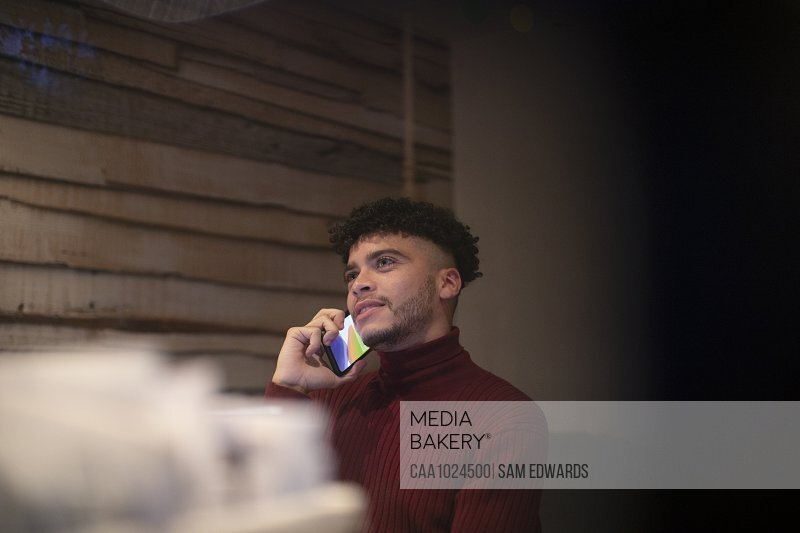 Young man talking on smart phone in home office