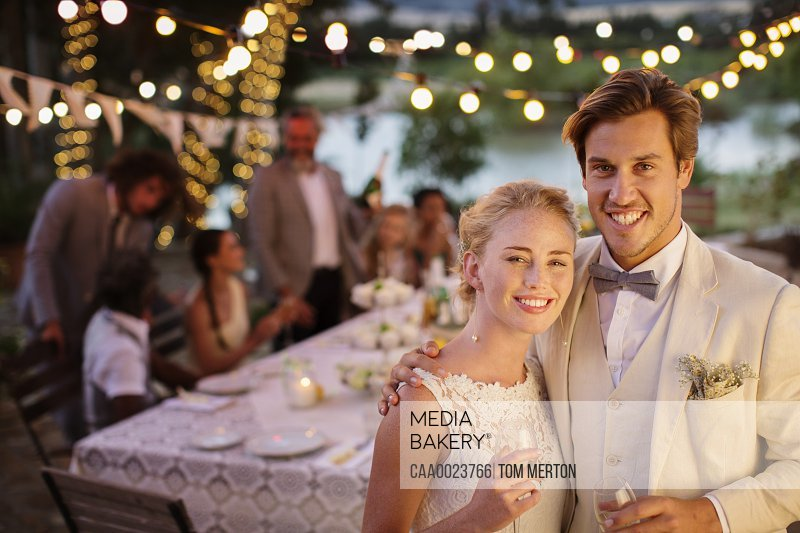 Portrait of young couple during wedding reception in domestic garden