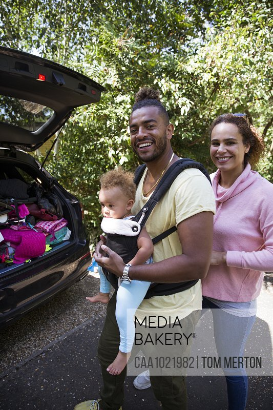 Portrait happy parents with toddler daughter outside car