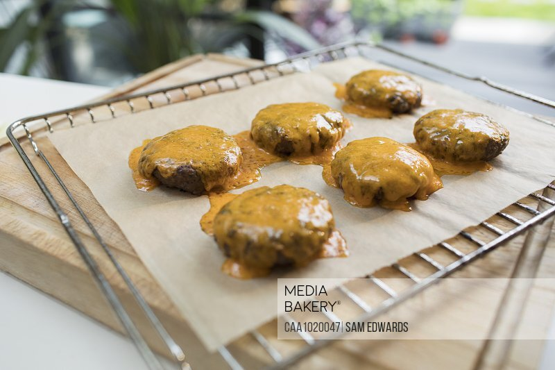 Close up cheeseburgers on cooling rack in kitchen