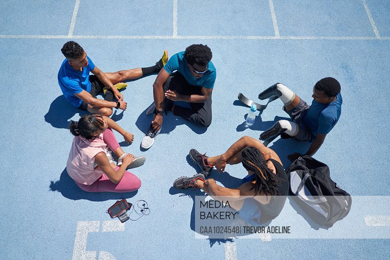 Young athletes talking on sunny blue sports track