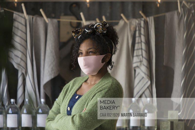Portrait confident female shop owner in pink face mask