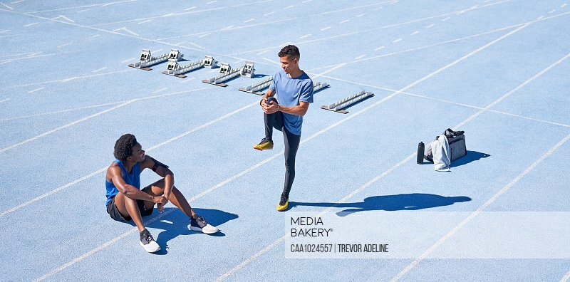Young male runners on sunny blue sports track
