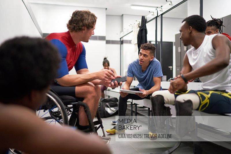 Paraplegic and amputee athletes talking in locker room