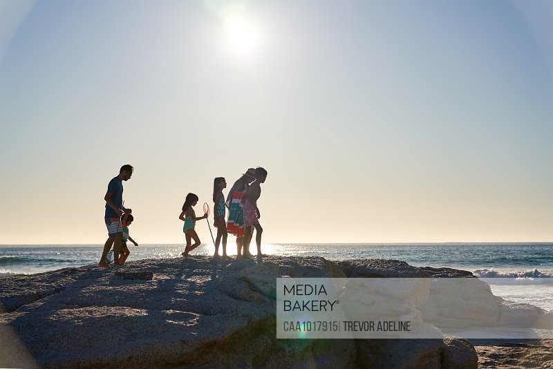 Family walking on rocks on sunny ocean beach, Cape Town, South Africa