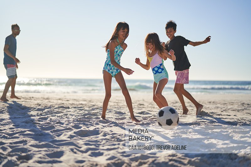 Happy family playing soccer on sunny beach