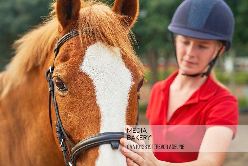 Teenage girl in equestrian helmet petting horse