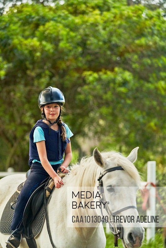 Portrait confident girl horseback riding