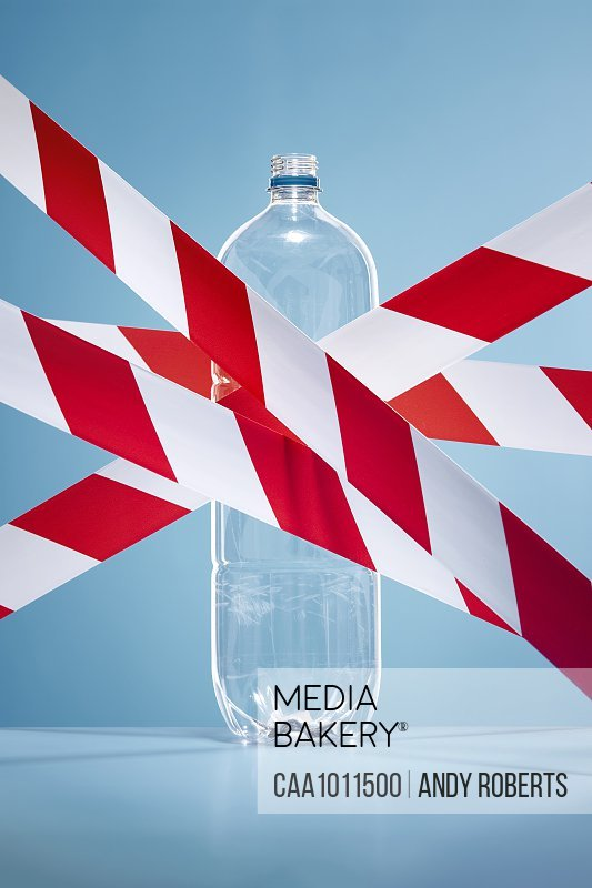Red and white tape covering plastic water bottle
