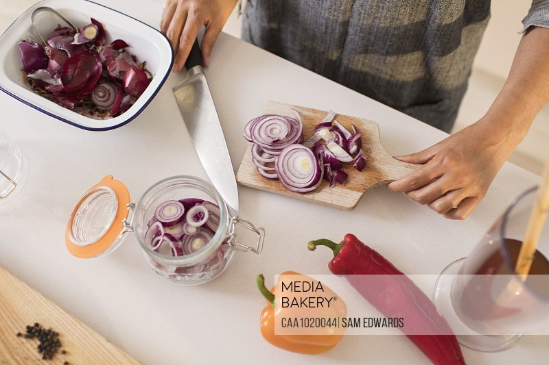 Woman slicing and preserving red onions at kitchen counter