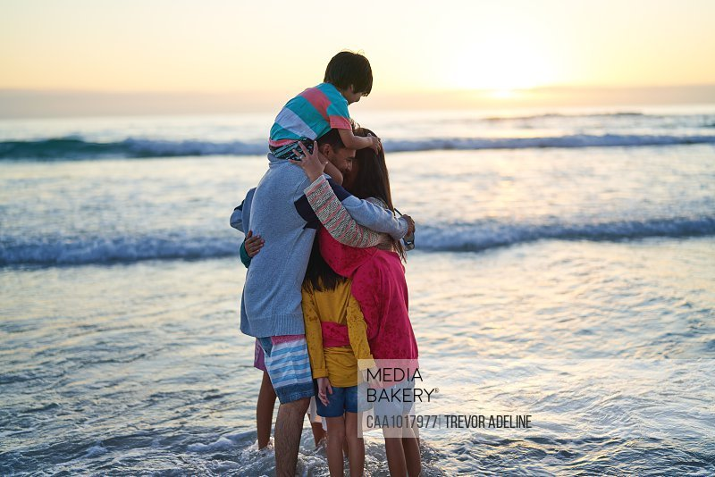 Happy affectionate family hugging in ocean surf at sunset