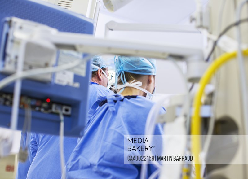 Rear view of doctors in operating theater medical equipment in foreground