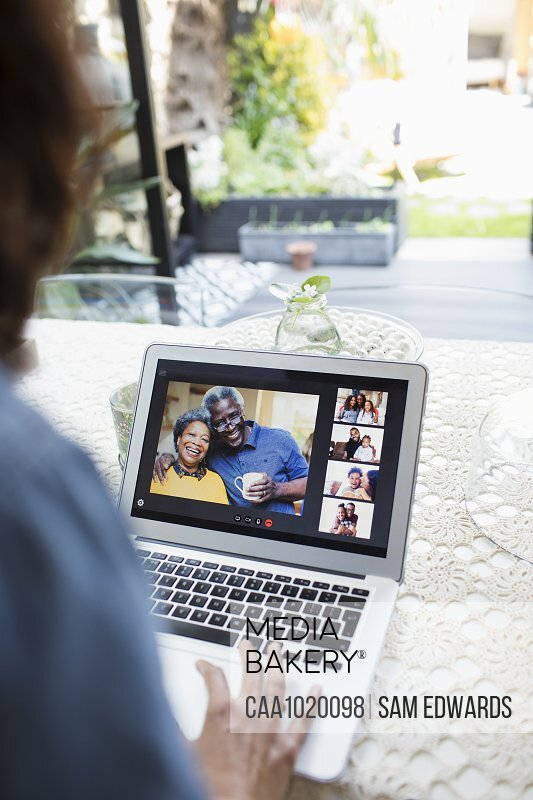 Woman video chatting with family and friends on laptop screen
