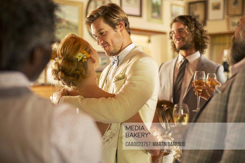 Bridegroom embracing bride during wedding reception in domestic room