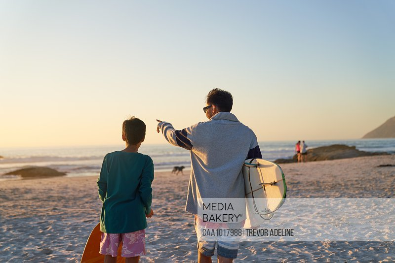 Father and son with surfboards on sunny beach