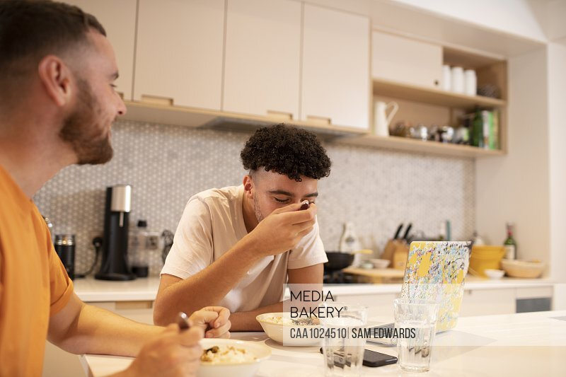 Gay male couple eating and using laptop at kitchen counter